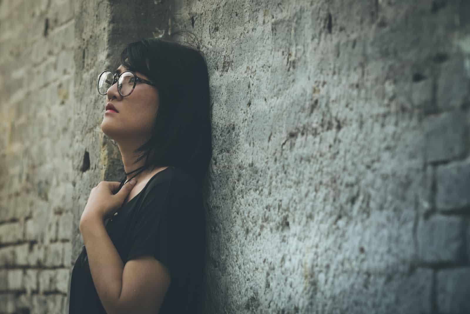 Eine verängstigte depressive Frau steht an der Wand gelehnt