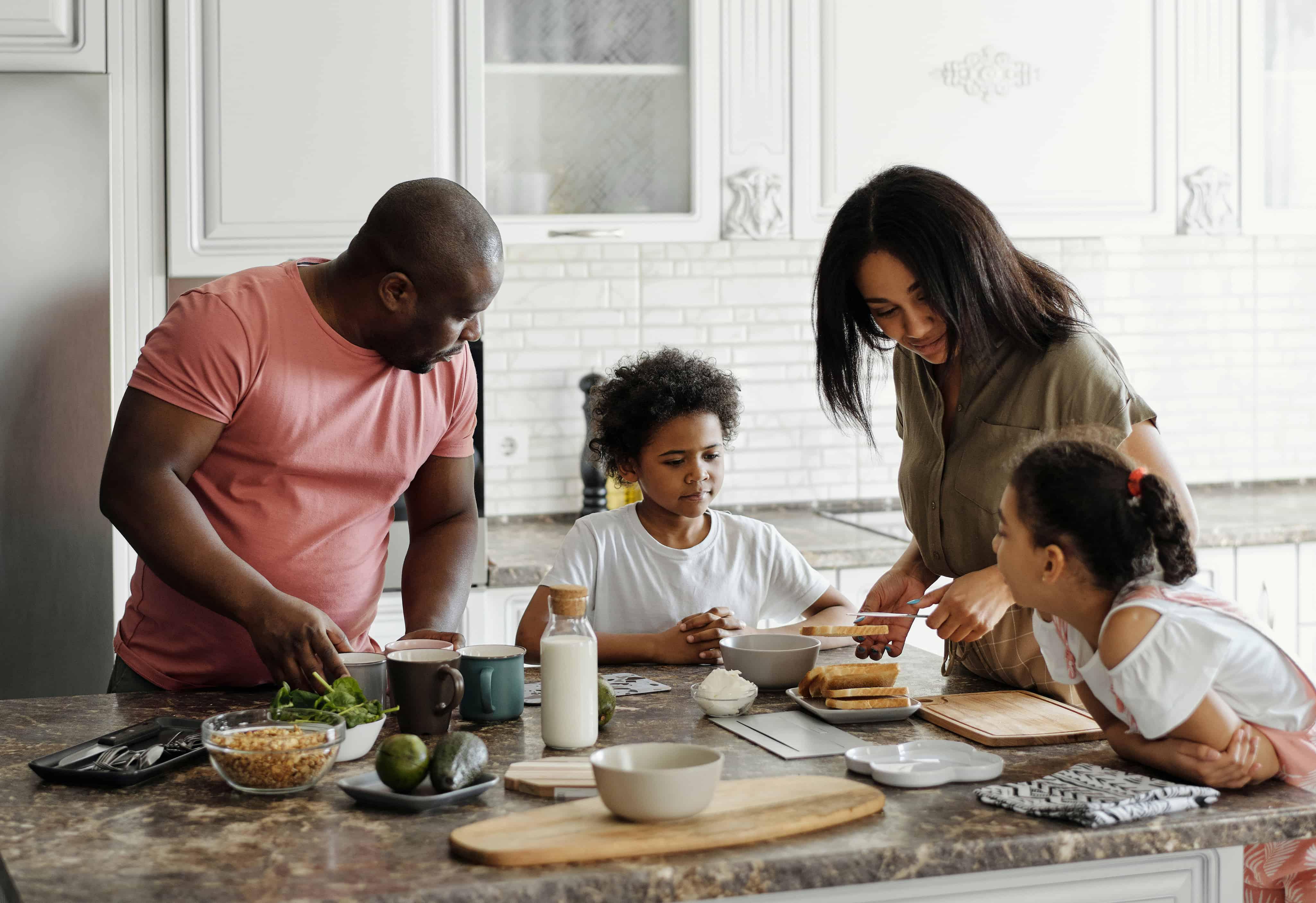 Eltern bereiten mit ihren Kindern das Frühstück in der Küche vor