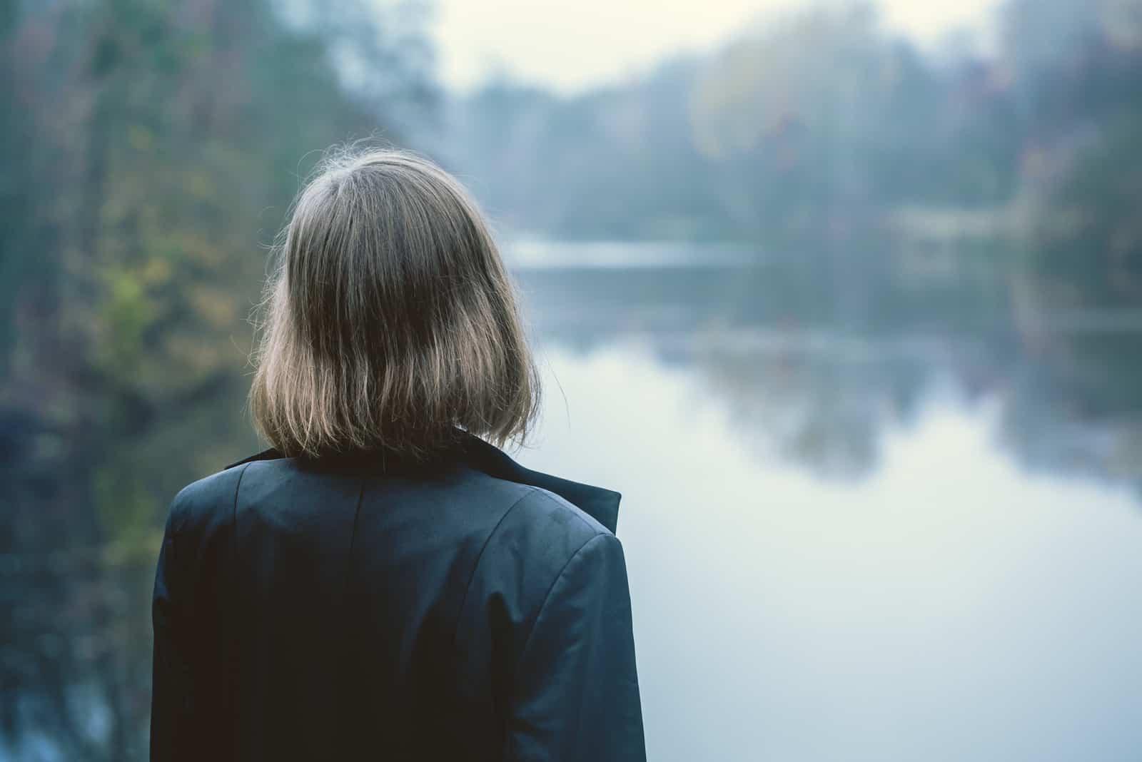 Frau allein am See stehen