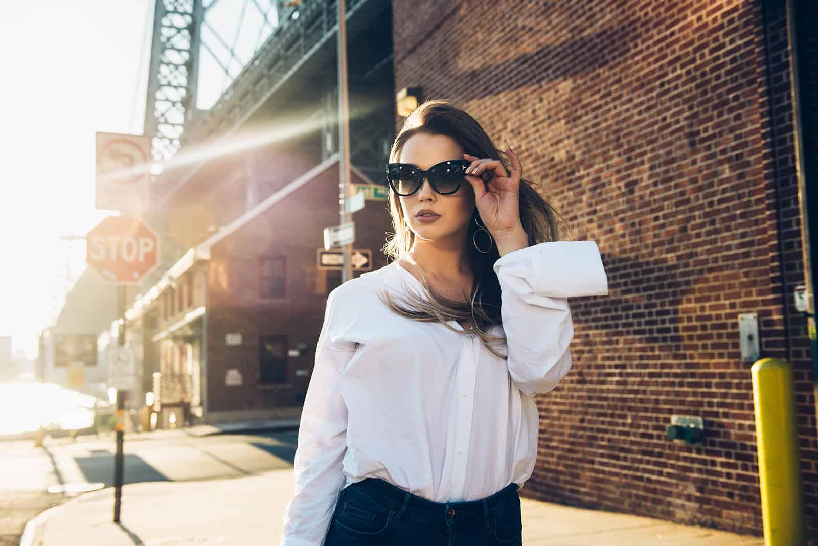 Frau berührt ihre Sonnenbrille, die alleine auf dem Bürgersteig geht
