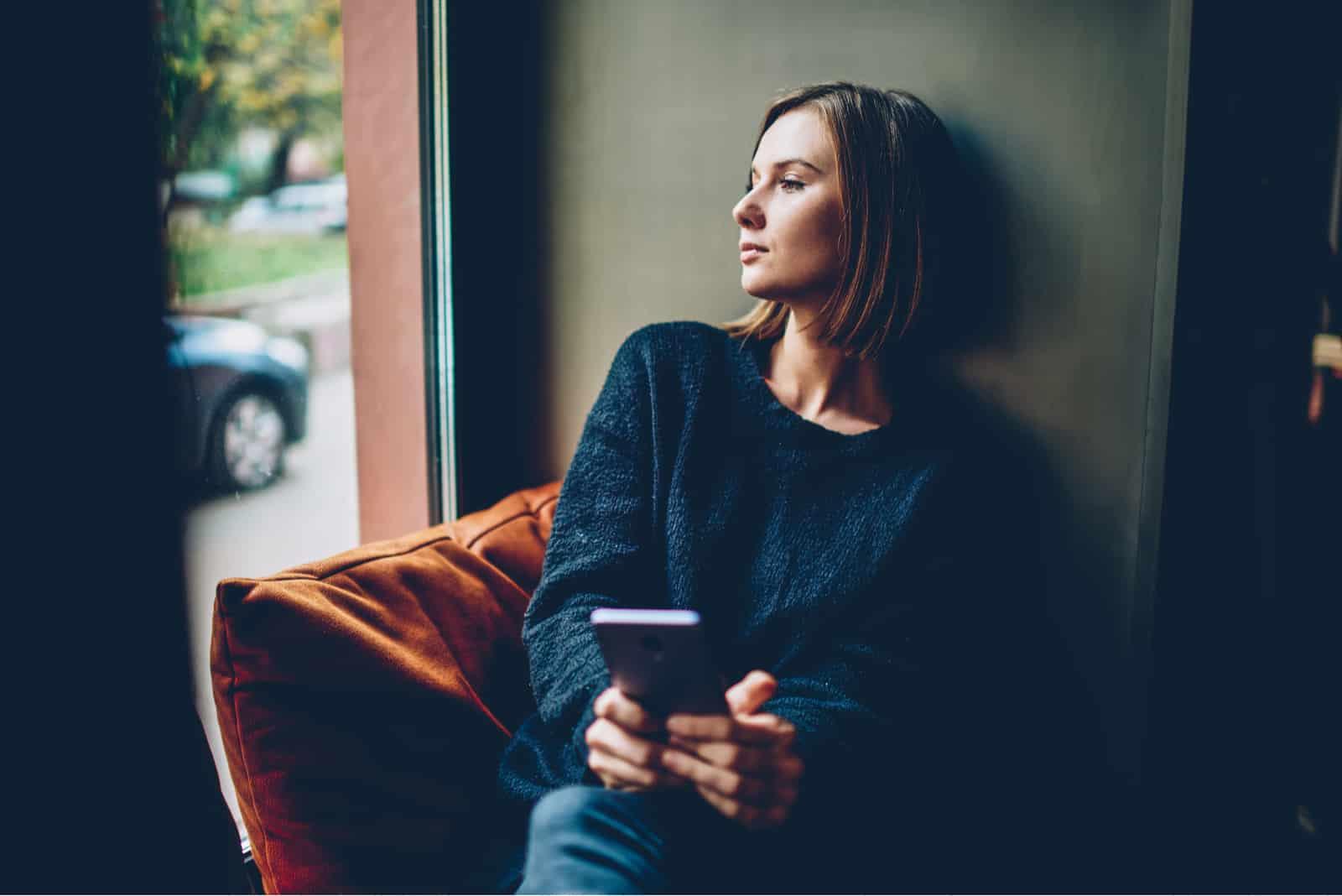 Frau gekleidet in schwarzem Freizeitoutfit, das aus dem Fenster schaut