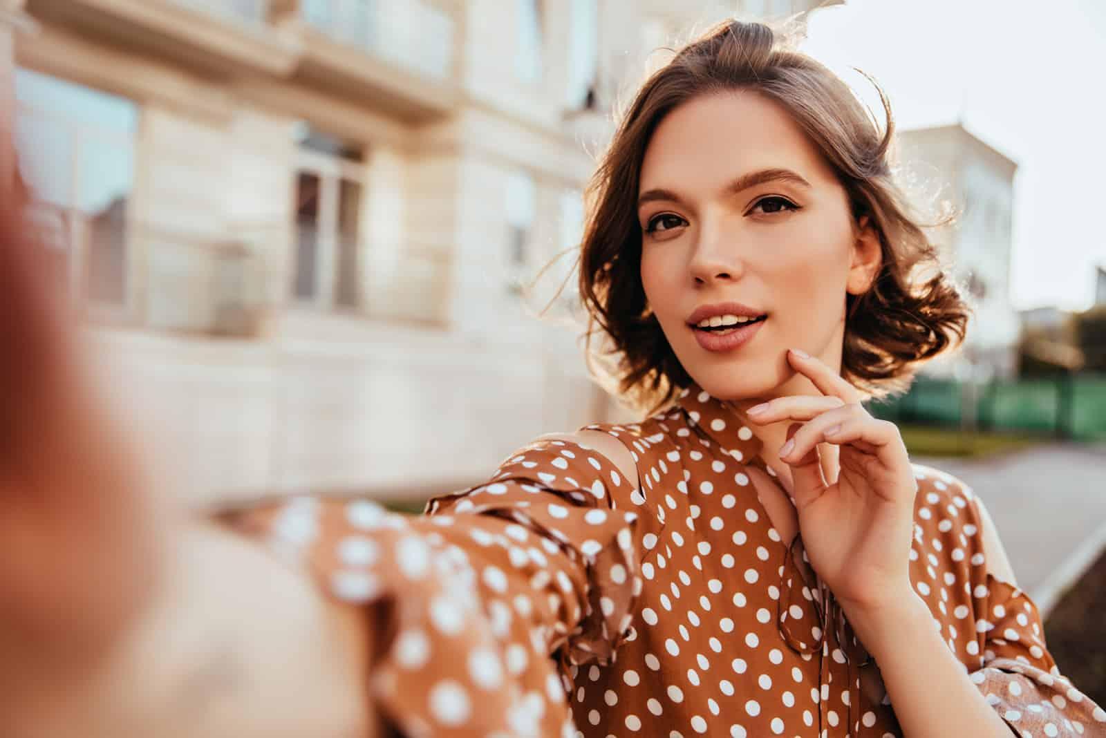 Frau in brauner Kleidung macht Selfie