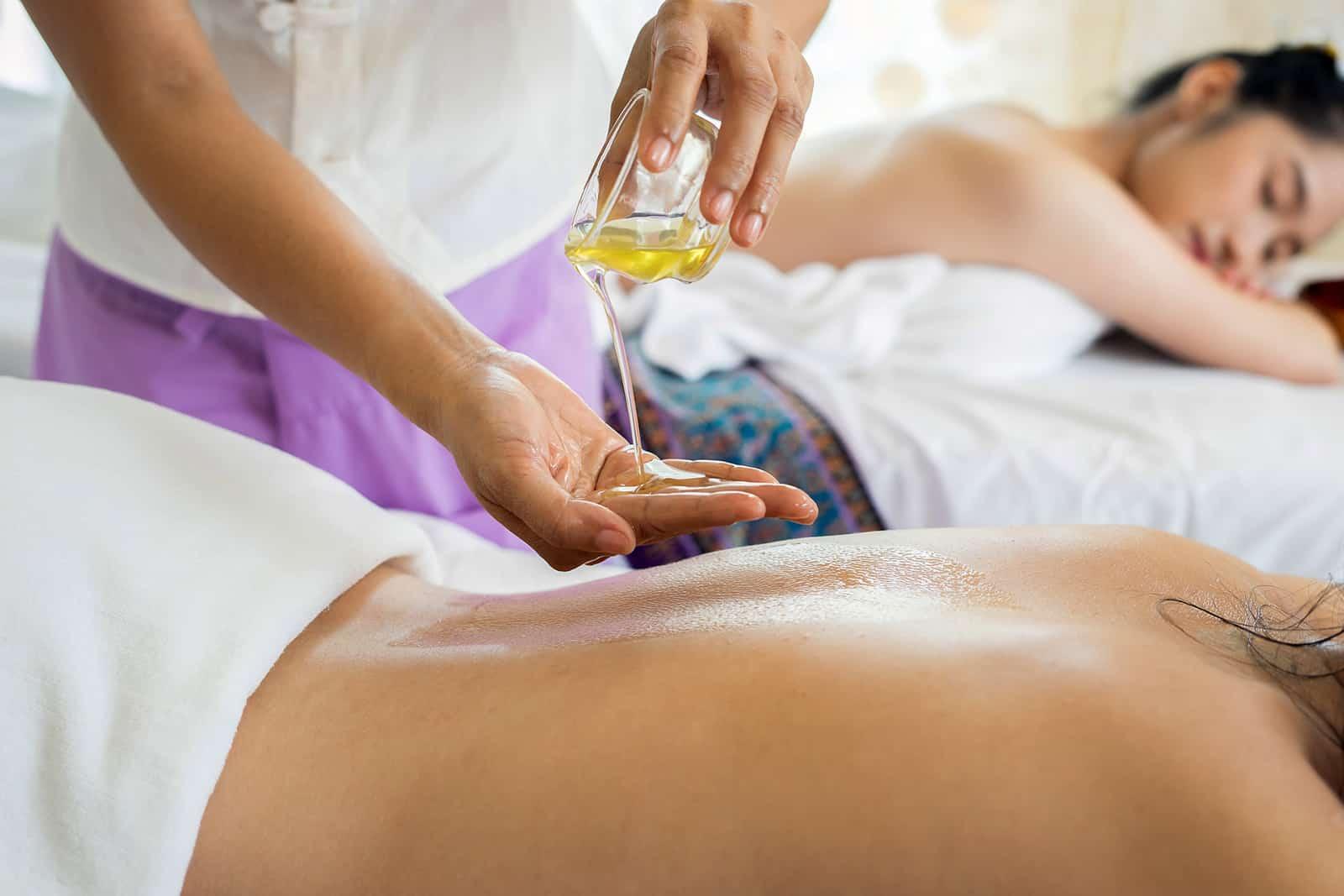 Frau, die auf dem Massagetisch liegt, während Massagegerät sich auf die Behandlung vorbereitet