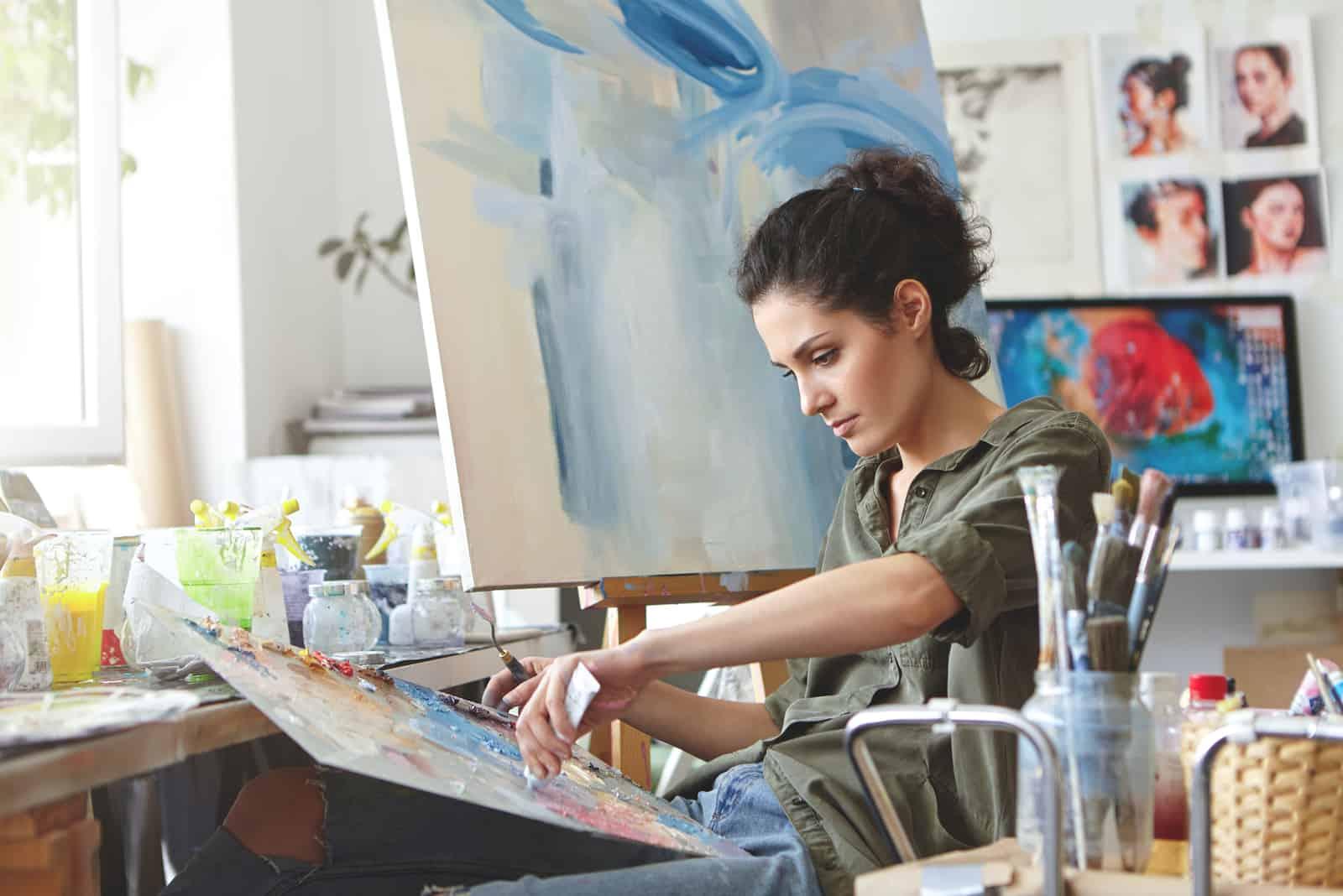 Frau mit dunklen Haaren, lässig gekleidet, malend