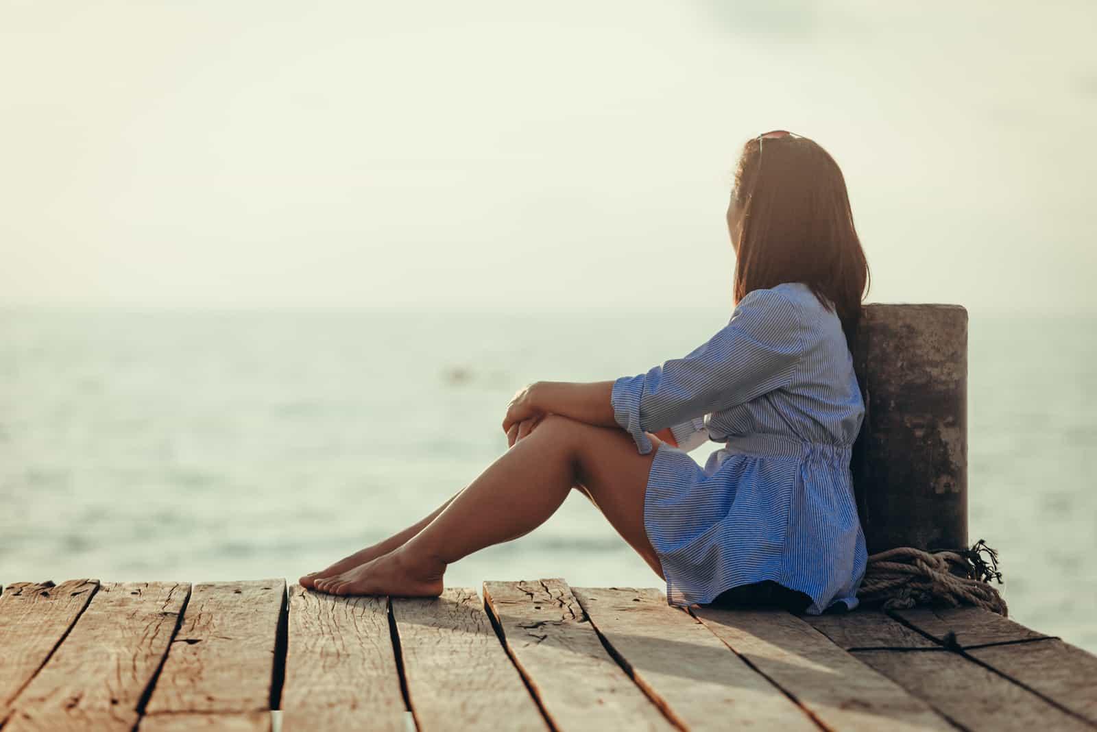 Frau sitzt allein einsam auf Holzbrücke