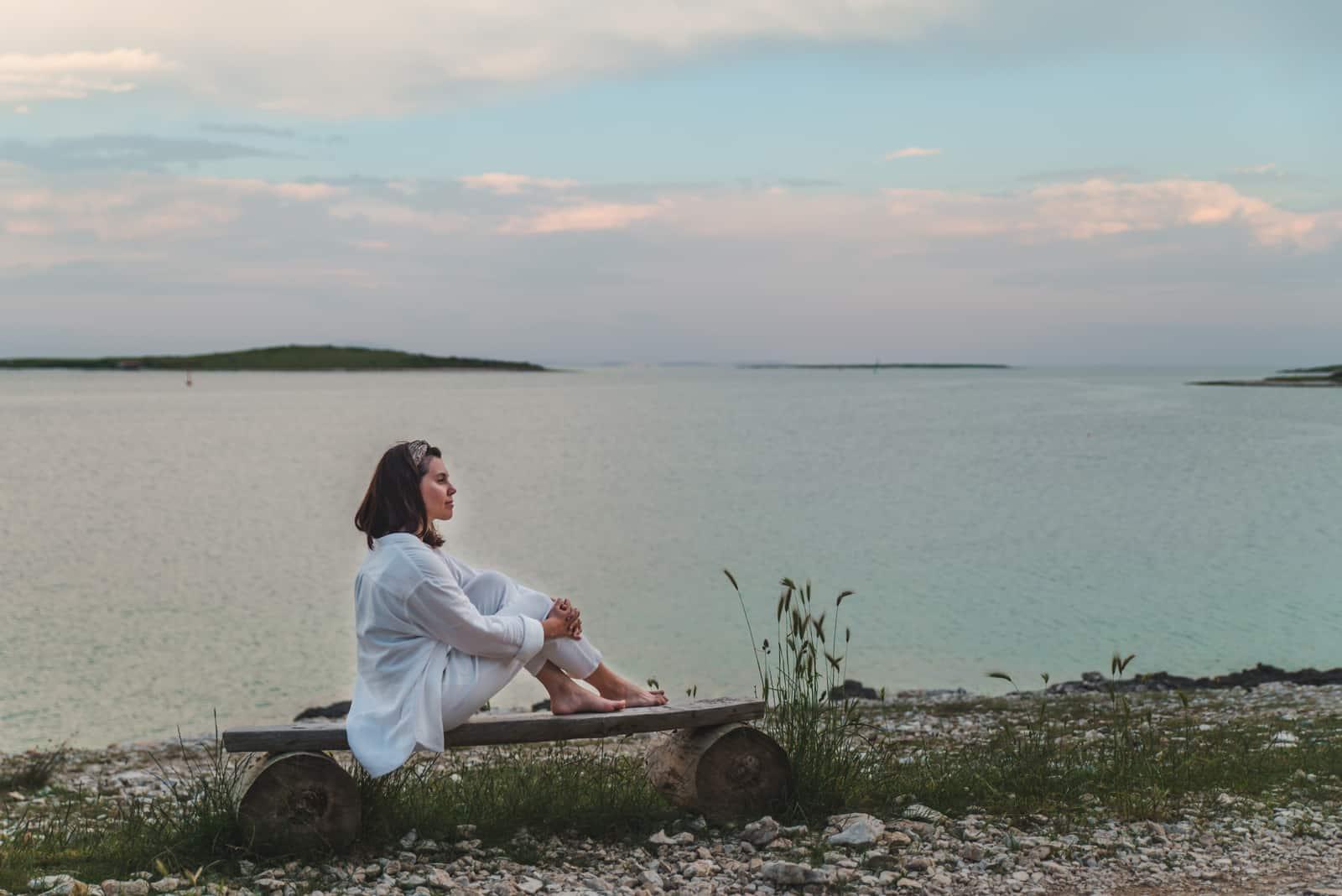 Frau sitzt auf Bank und schaut auf Sonnenuntergang über dem Meer