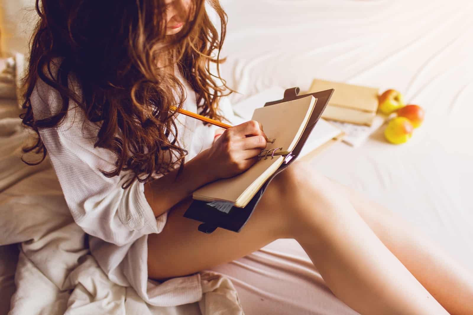 Frau sitzt auf ihrem gemütlichen Bett und macht sich Notizen