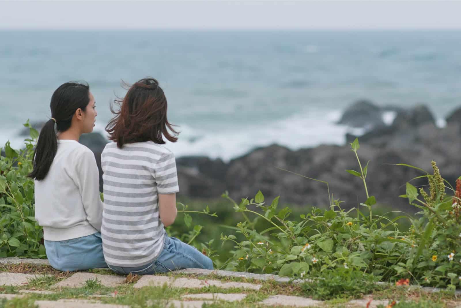 Frauen plaudern und sitzen am Meer