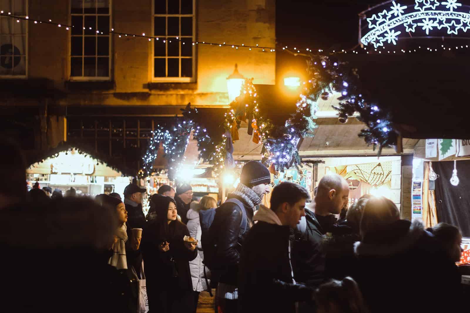 Gruppe von Menschen, die abends auf dem Weihnachtsmarkt spazieren gehen