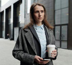 eine Frau, die mit Kaffee in der Hand geht