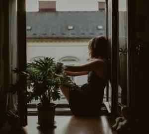 Eine Frau sitzt auf der Fensterbank in ihrer Wohnung