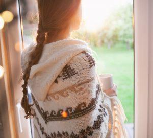 Frau, die durch Fenster während des Tages schaut