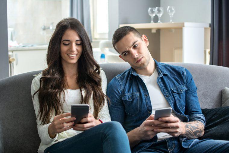 Ein eifersüchtiger Mann schaut auf das Handy seiner Freundin