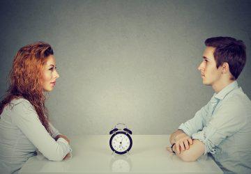 Ein Mann und eine Frau sitzen während eines Speed-Dates am Tisch