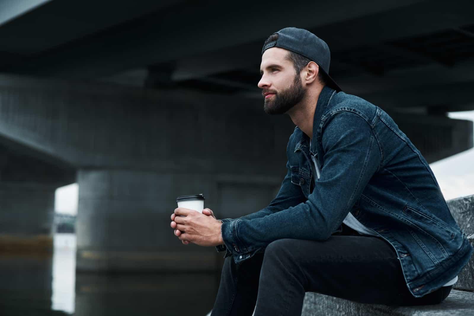 Junger stilvoller Mann, der auf Treppen auf Stadtstraße hält, die Tasse hält heißen Kaffee