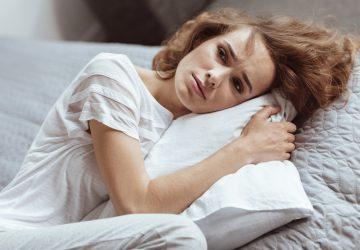 ein trauriges Mädchen, das ein Kissen umarmt