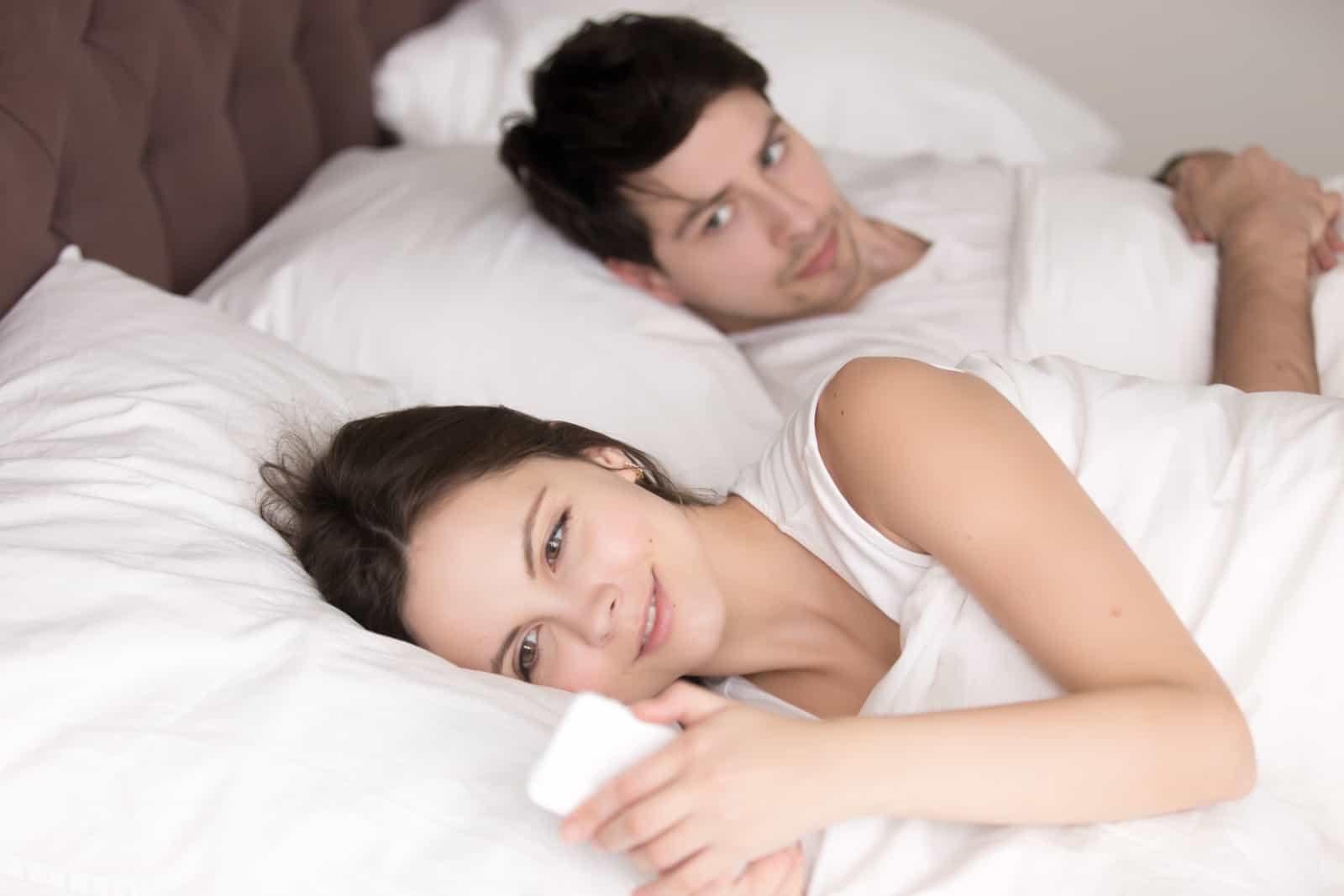 Mädchen, das Nachrichten auf Handy schreibt, während mit Mann im Bett liegend