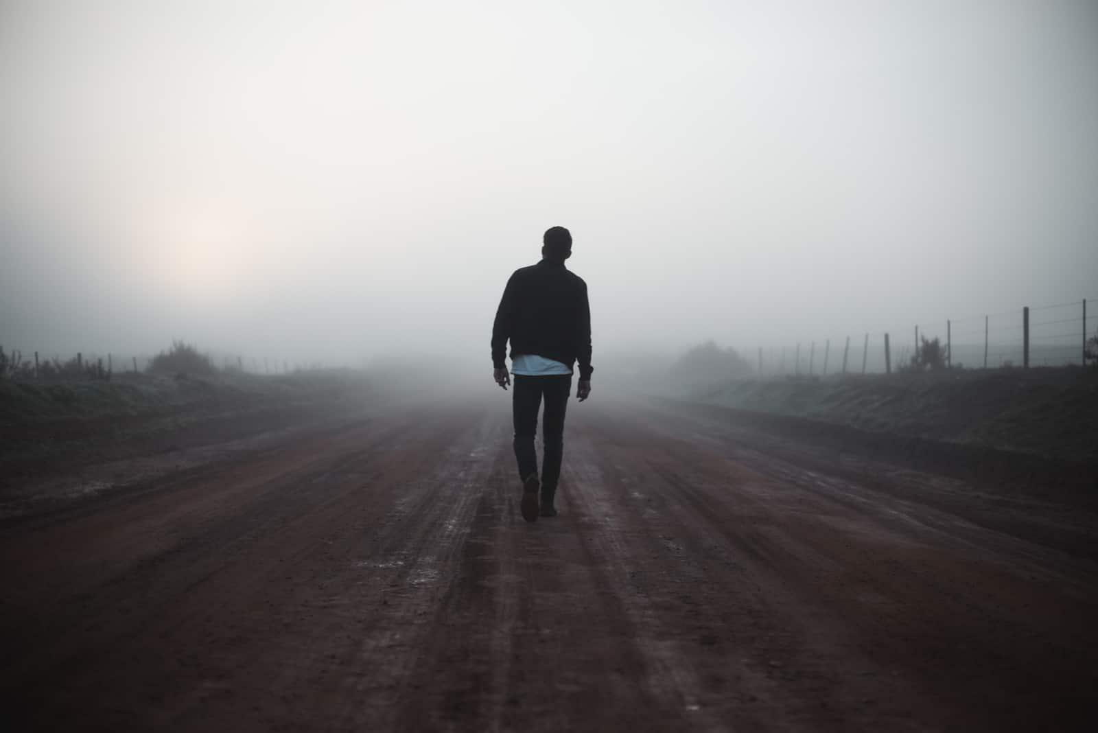 Mann, der auf nebliger Straße weggeht