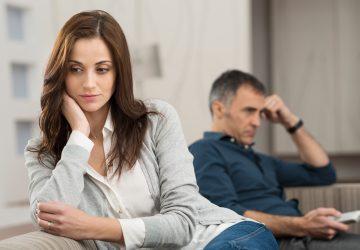 eine nachdenkliche Frau, die sich von ihrem Mann abwendet und fernsieht