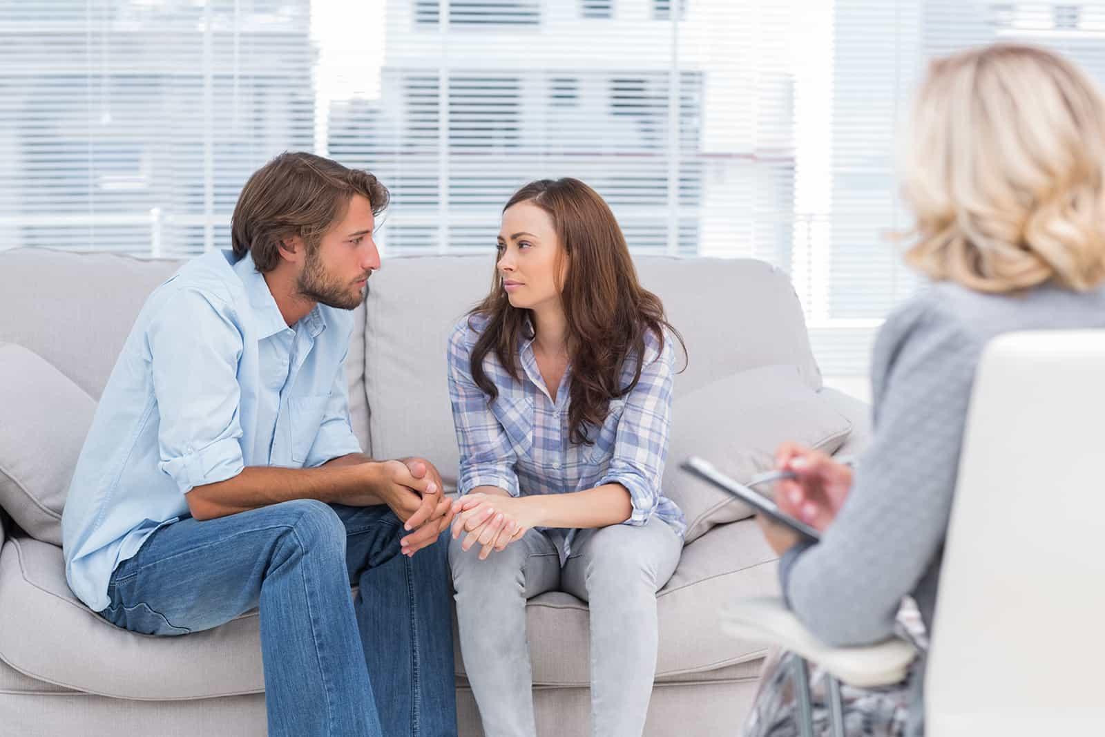 Paar, das sich während einer Therapiesitzung ansieht, während Therapeut vor ihnen sitzt