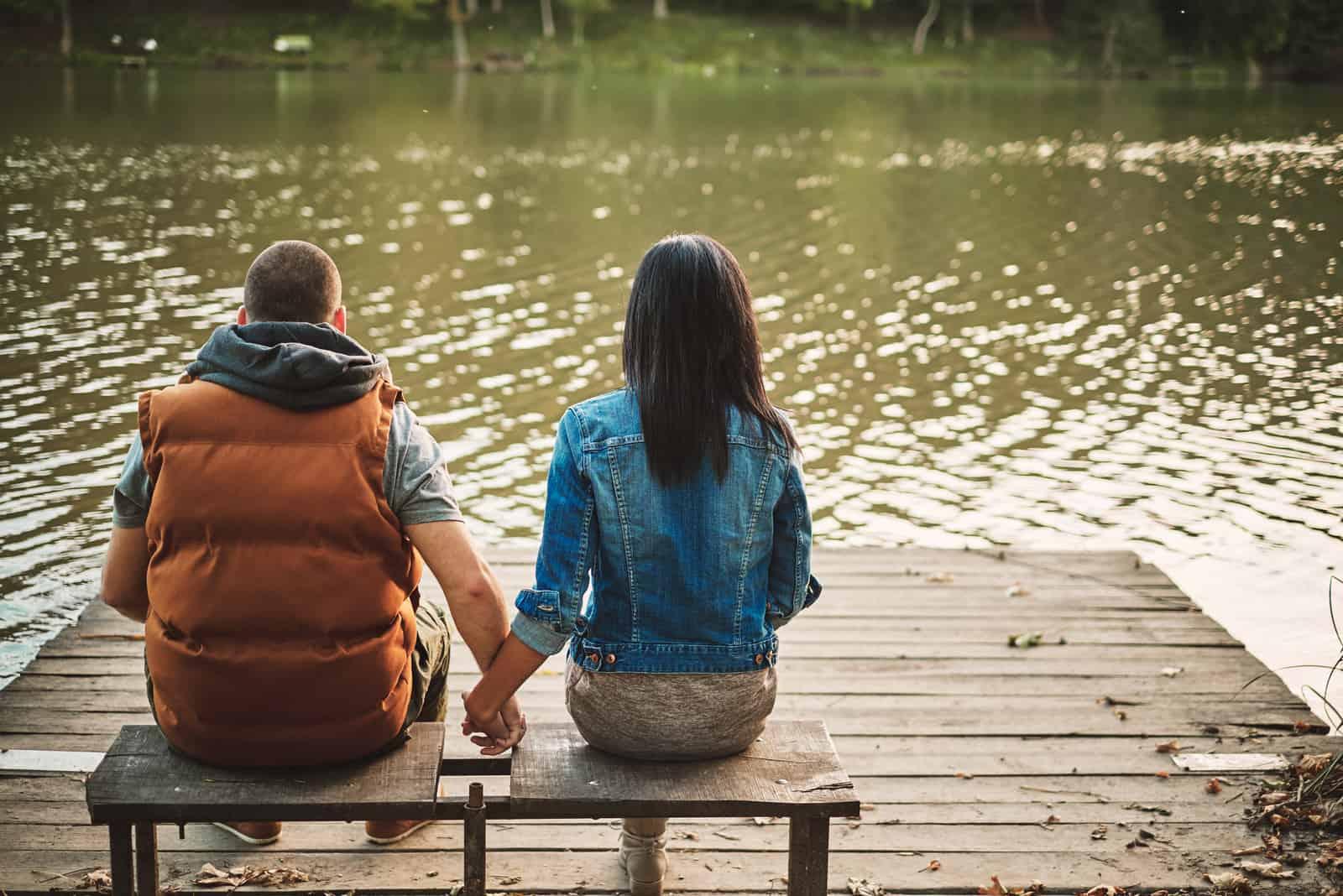 Paar sitzt auf der Bank am See