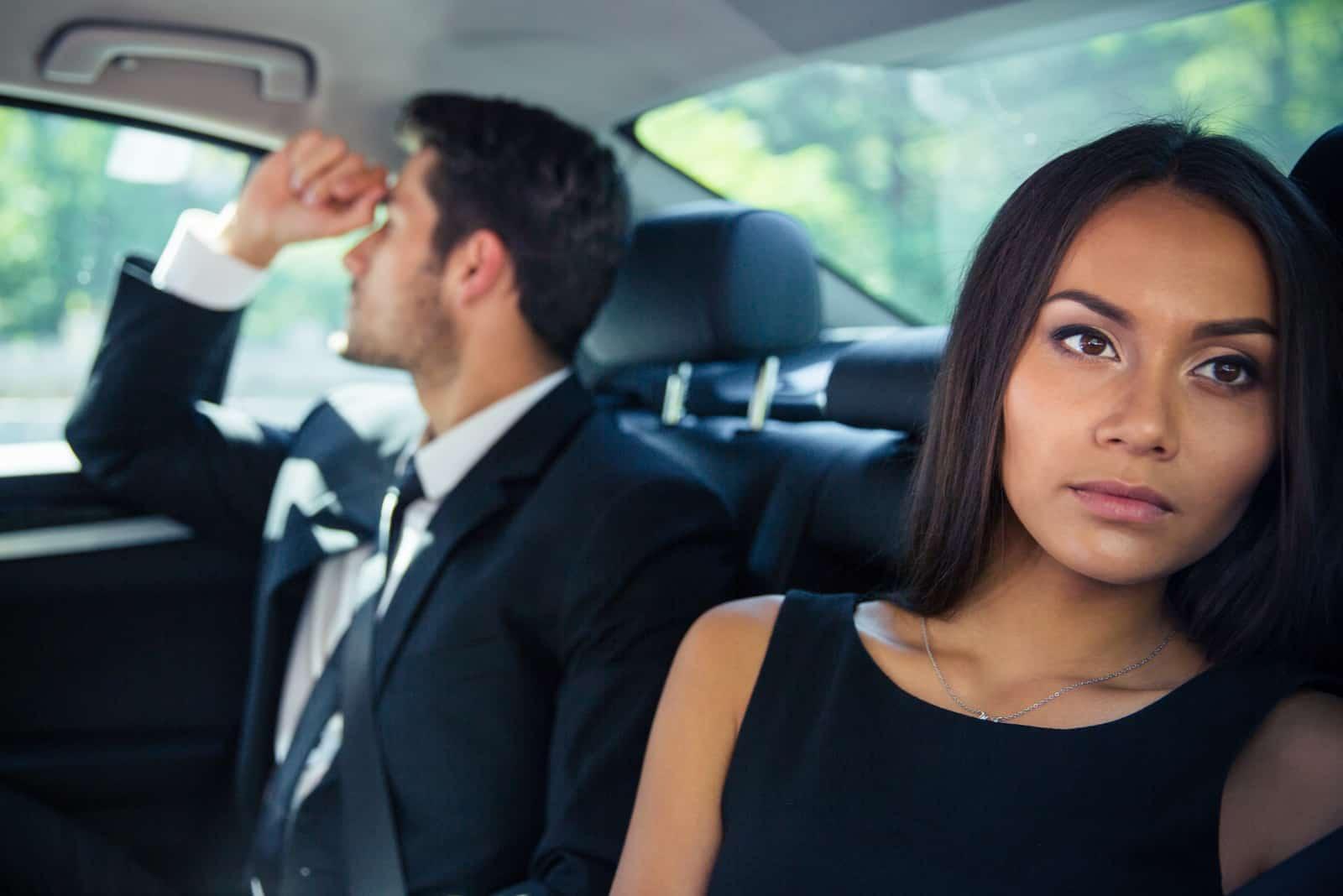 Paar sitzt im Auto und ignoriert sich gegenseitig