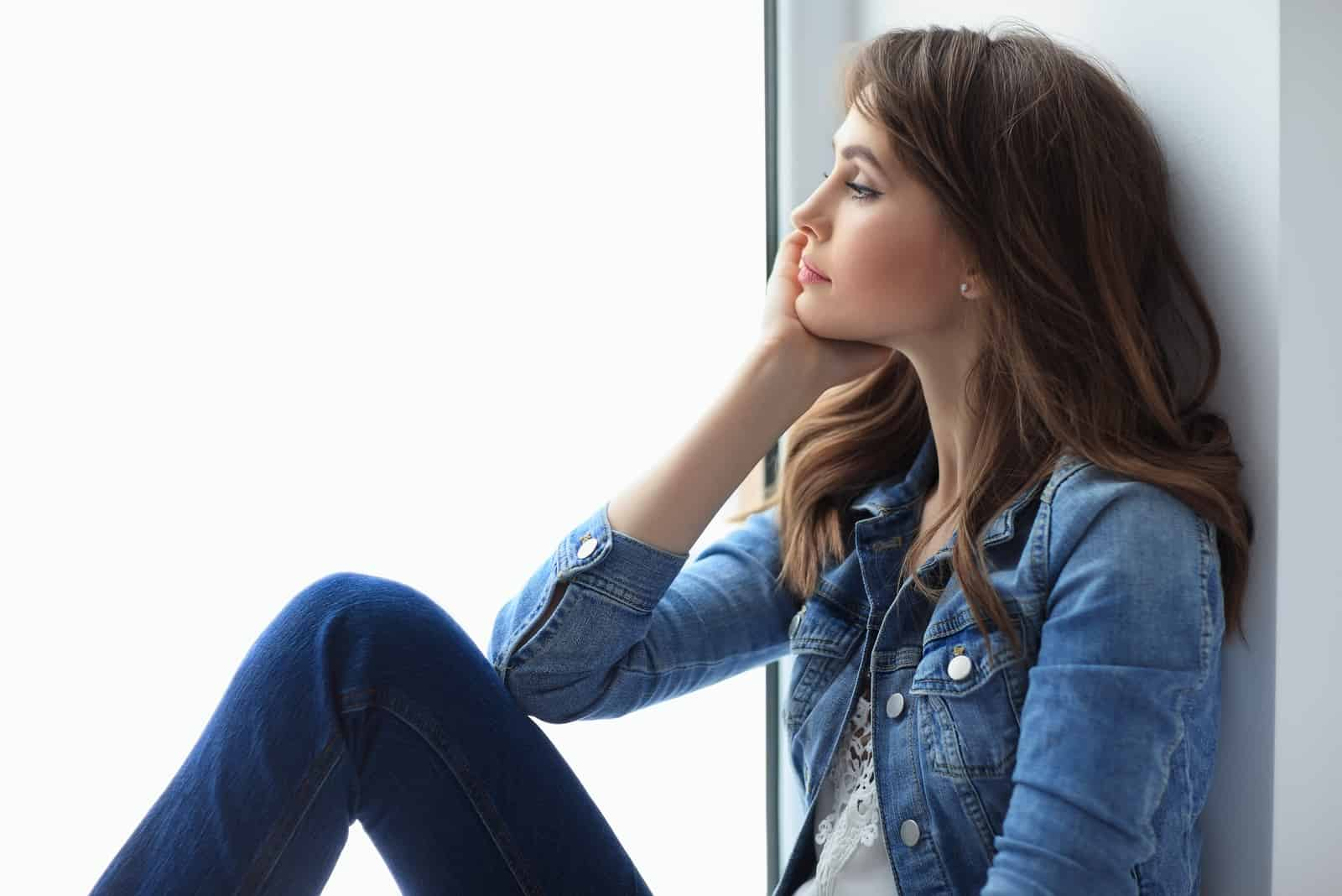 Porträt der schönen nachdenklichen Frau, die auf Fensterbank entspannt