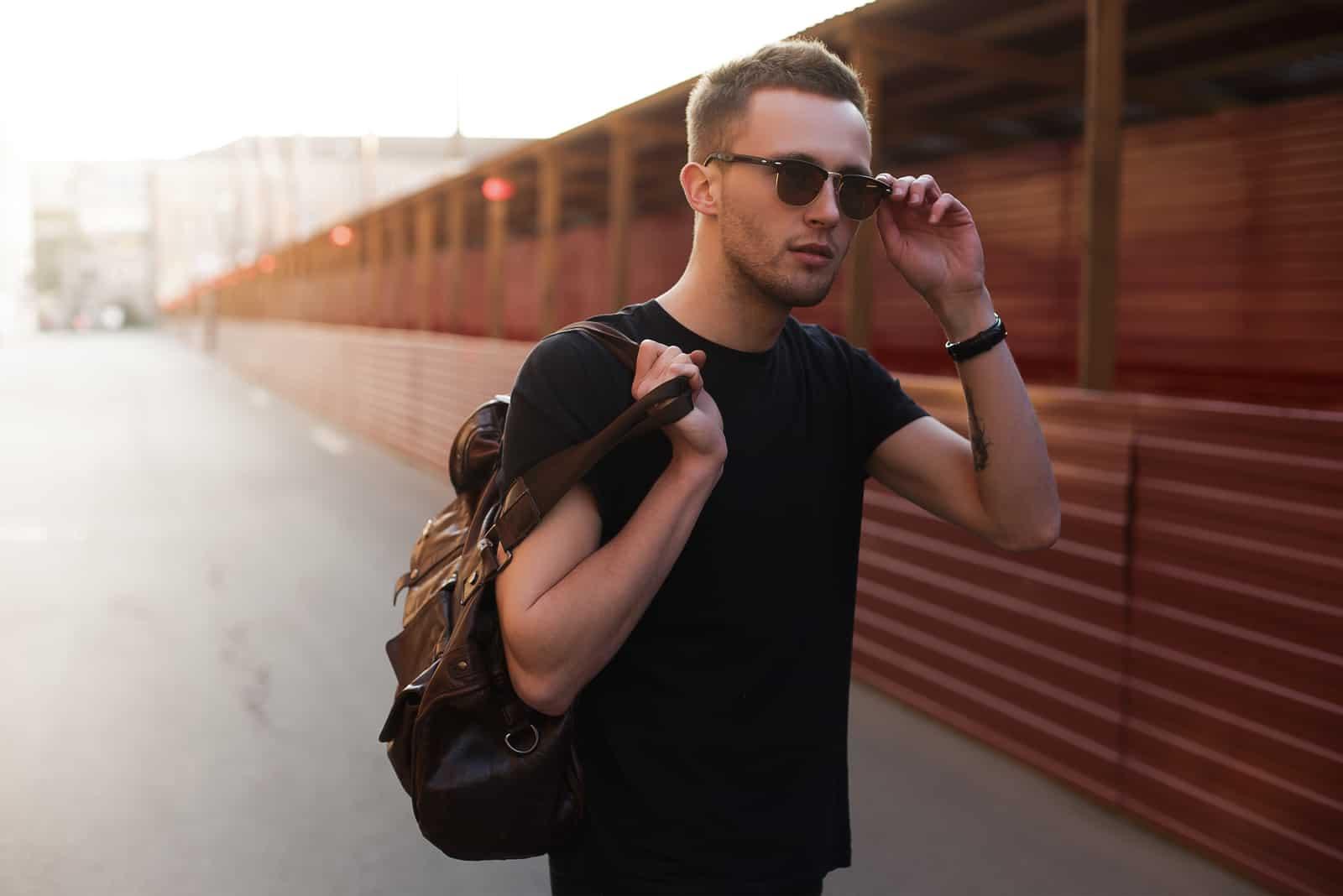 Porträt des jungen stilvollen Mannes mit Tasche in der Straße