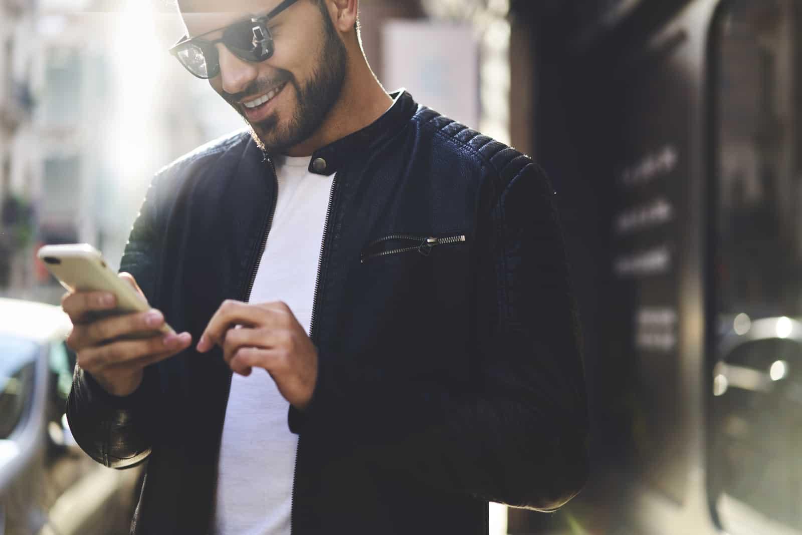 Porträt des lächelnden gutaussehenden trendig gekleideten Hipster-Kerls mit Handy