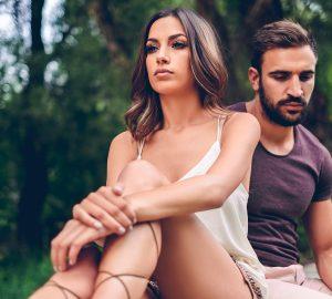 Ein nachdenklicher Mann und eine Frau sitzen auf dem Dock