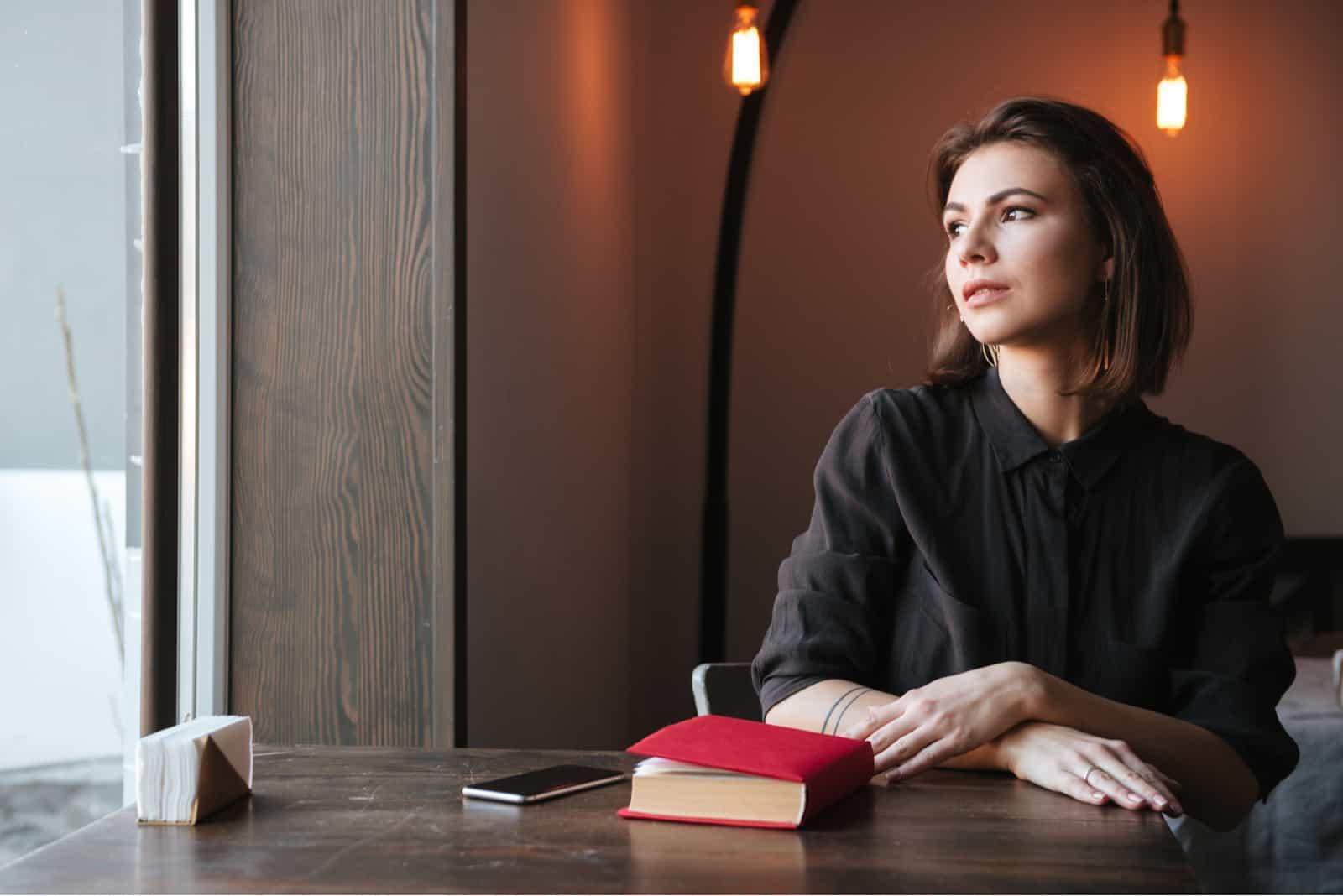 Frau sitzt am Tisch in der Nähe von Buch und Telefon im Café