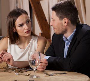 lächelnder Mann, der eine ernste Frau betrachtet, die mit ihm in einem Restaurant sitzt