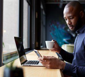 Ein Mann, der im Café sitzt und sein Smartphone überprüft