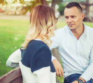 Ein Mann spricht mit einer Frau, die neben ihm auf der Bank sitzt