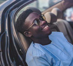 lächelnder Mann, der Sonnenbrille trägt, die im Fahrzeug sitzt