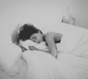 eine Frau, die im Bett liegt und ein Kissen umarmt