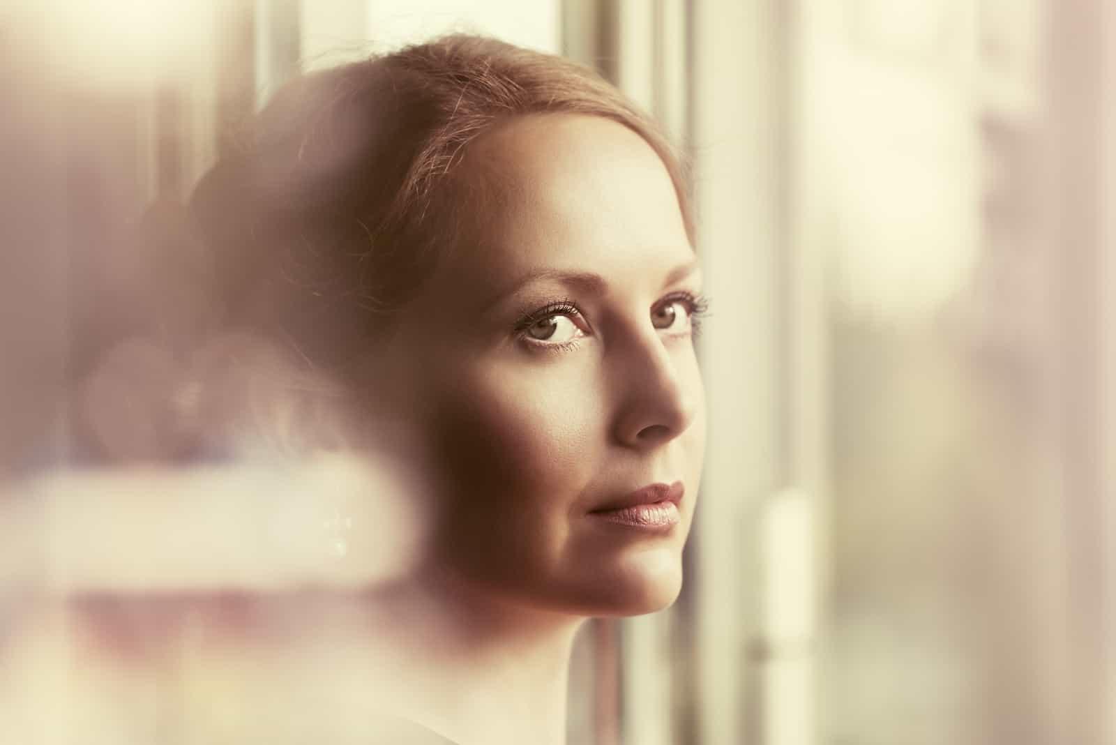 Traurige schöne Frau, die aus dem Fenster schaut