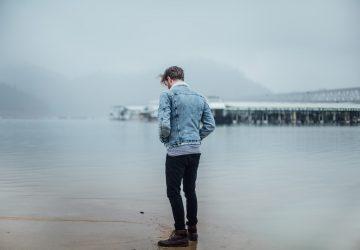 ein nachdenklicher Mann, der am Strand steht