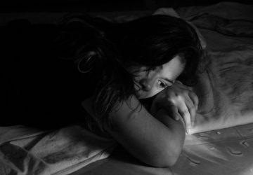 ein trauriges Mädchen, das auf dem Bett liegt