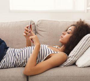 Frau Messaging auf dem Smartphone zu Hause