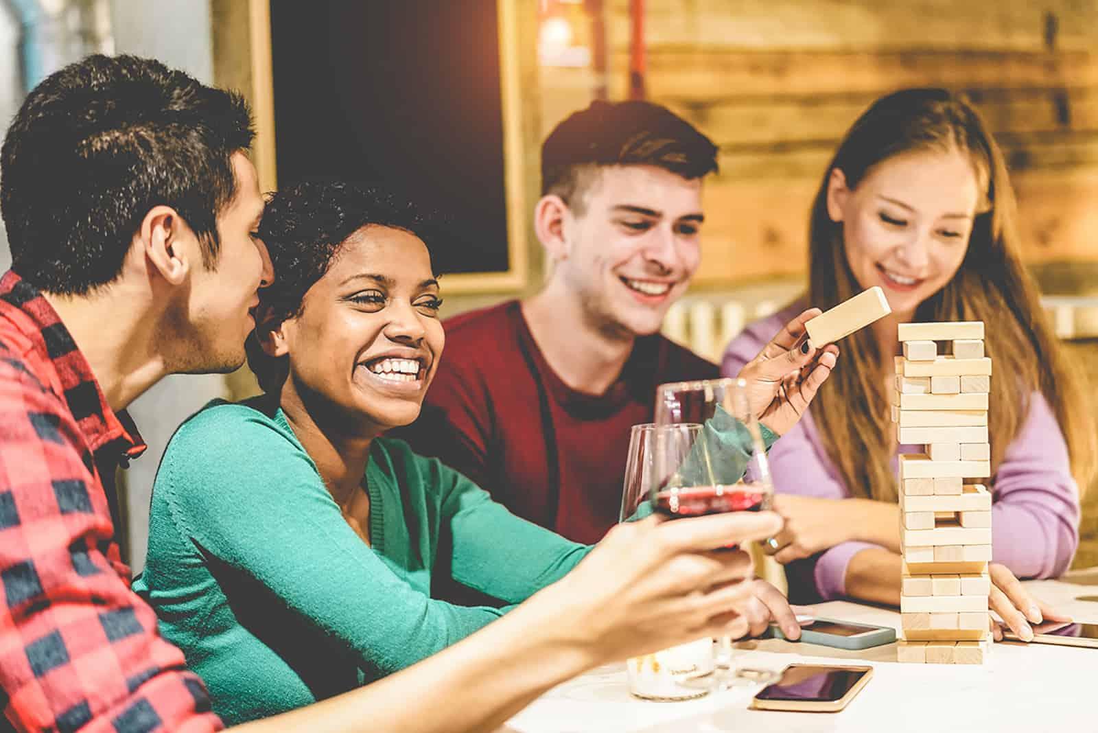 Zwei Paare spielen zu Hause ein Jenga-Spiel und trinken Wein