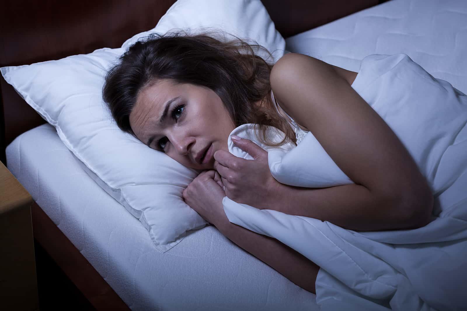 ängstliche Frau, die versucht zu schlafen und das Laken festhält