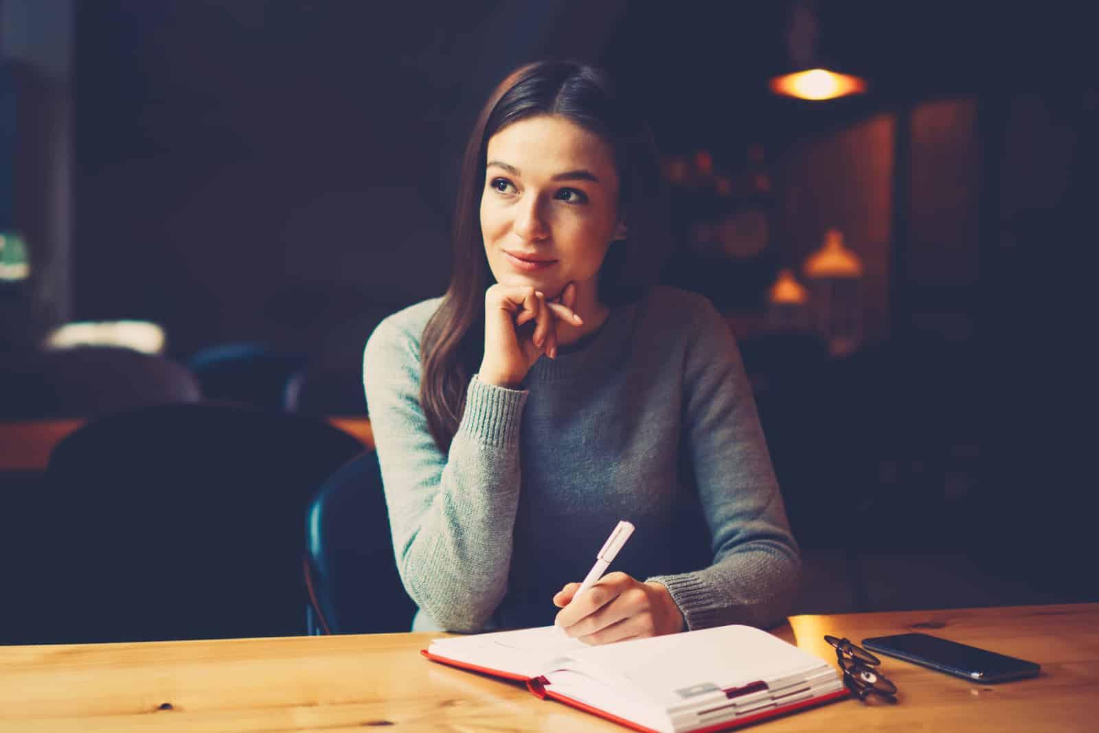 attraktive junge Frau mit Stift in der Hand, die über Pläne nachdenkt und Liste schreibt, um zu tun