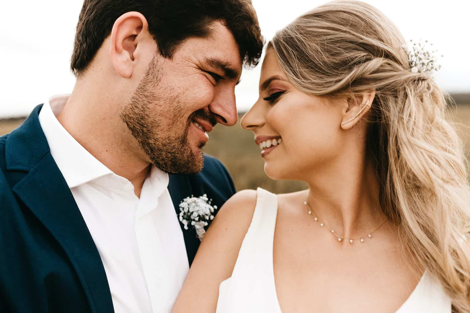 ein Hochzeitspaar, das sich gegenübersteht und lächelt