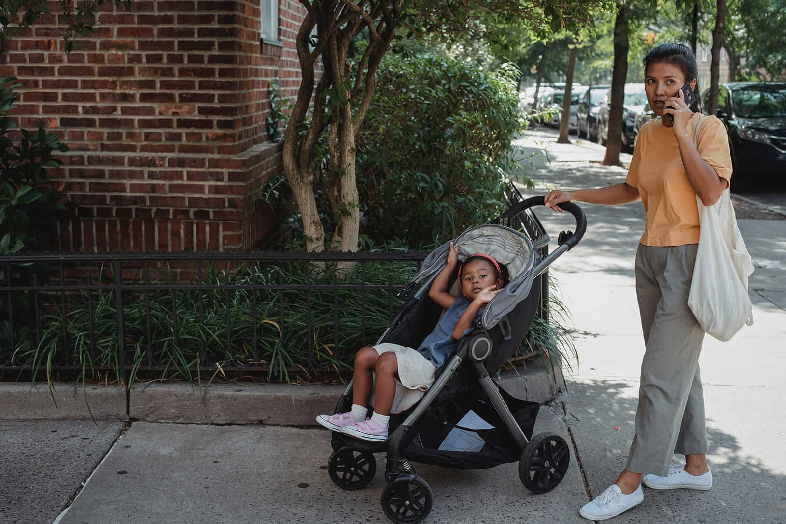 ein Kind, das in einem Kinderwagen sitzt, während Mutter einen Anruf auf der Straße hat