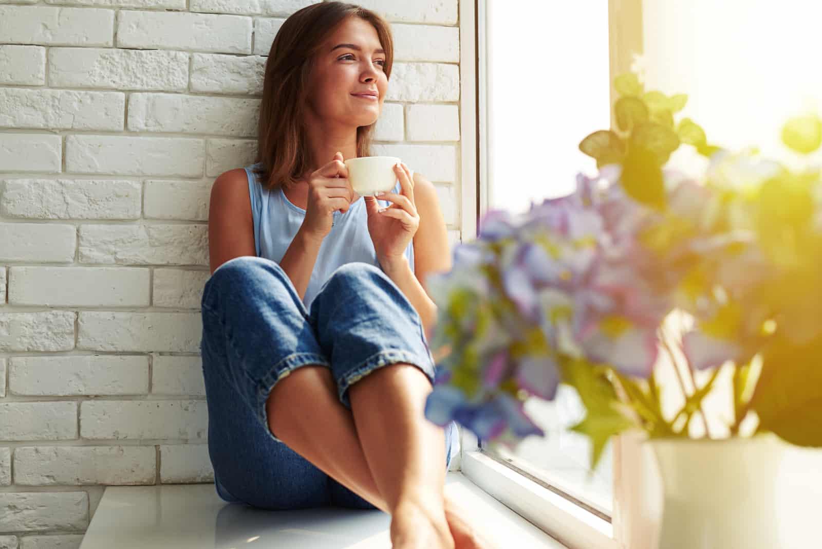 ein Mädchen, das am Fenster sitzt und Kaffee trinkt