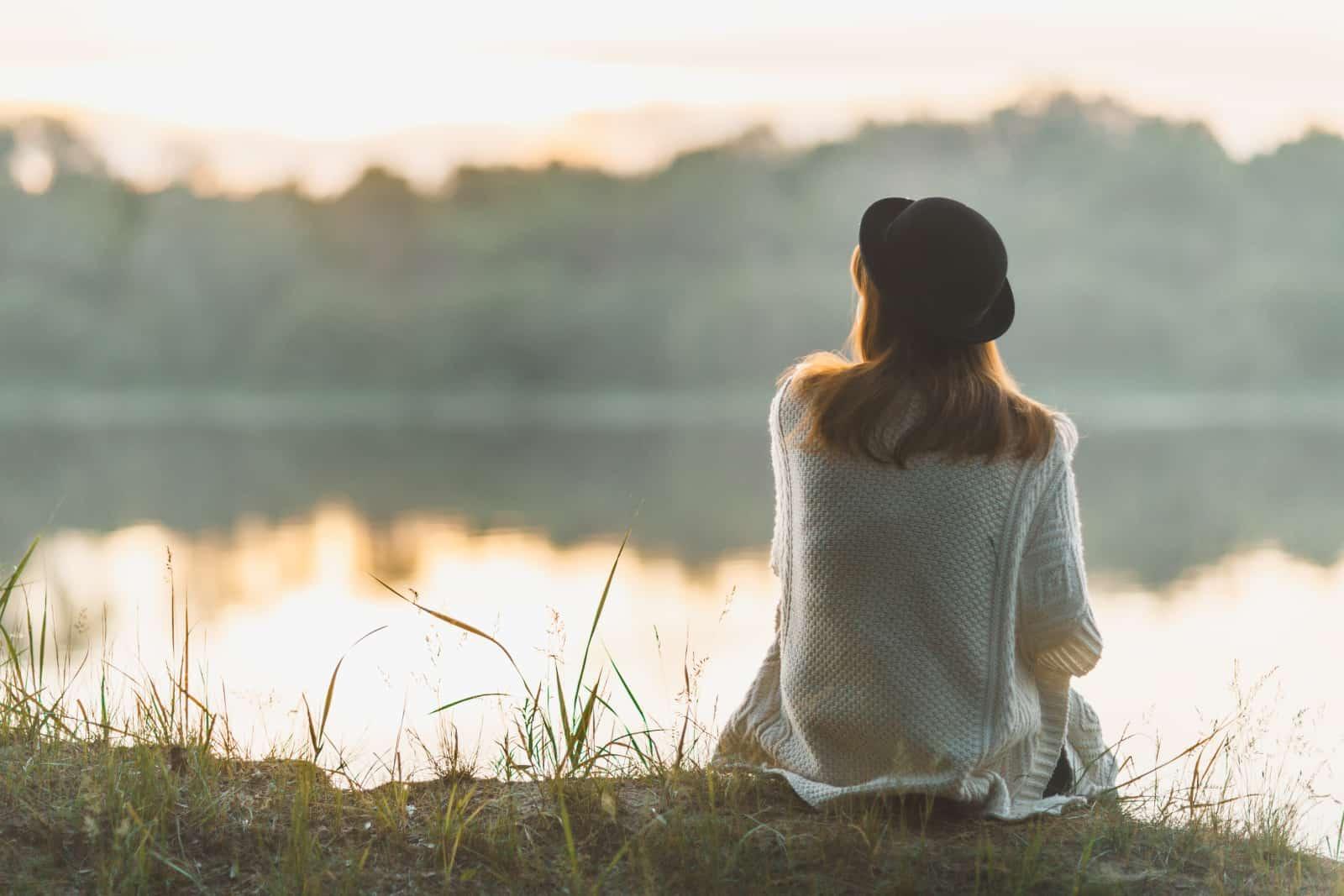 ein Mädchen, das am Ufer eines Flusses sitzt