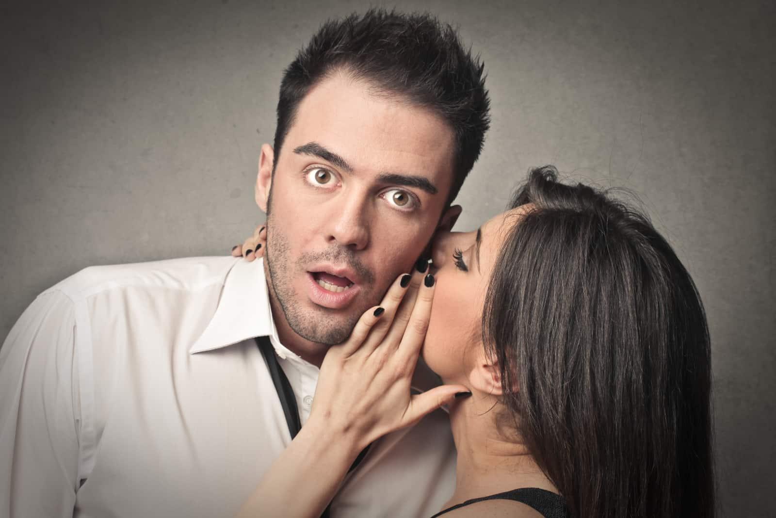 ein Mädchen flüstert einem Mann ins Ohr