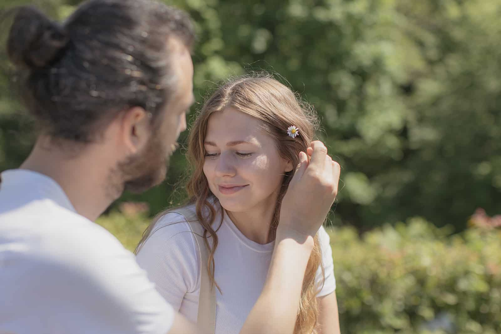 ein Mann, der Blume in ein Haar der lächelnden Frau setzt, während er in der Natur sitzt