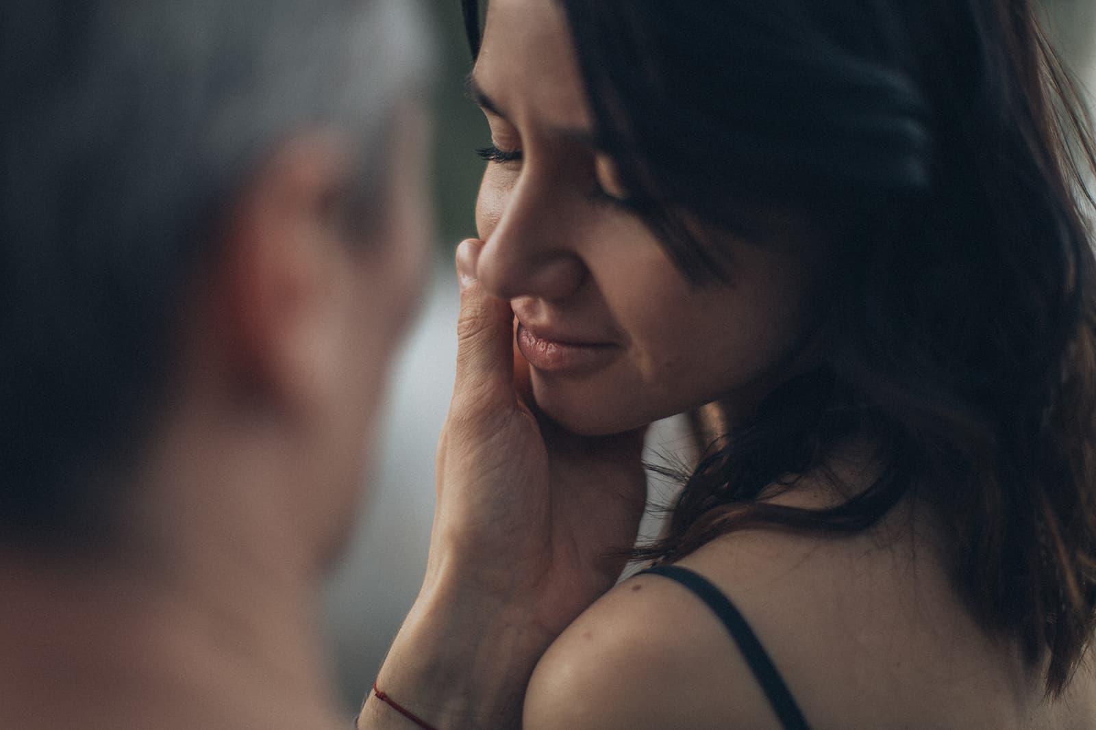 Ein Mann berührte das Gesicht seiner Freundin, die ihre Augen schloss